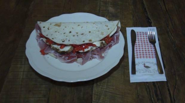 A piadina campagnola leva mozzarella de búfala, mozzarella defumada, tomate e speck